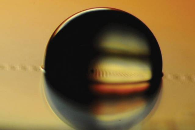 Photo shows a water droplet sitting on a ferrofluid-impregnated surface, which has cloaked the droplet with a very thin layer. Image courtesy of the researchers - Click to see VIDEO