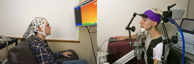 n this photo, UW students Darby Losey, left, and Jose Ceballos are positioned in two different buildings on campus as they would be during a brain-to-brain interface demonstration. The sender, left, thinks about firing a cannon at various points throughout a computer game. That signal is sent over the Web directly to the brain of the receiver, right, whose hand hits a touchpad to fire the cannon.Mary Levin, U of Wash.