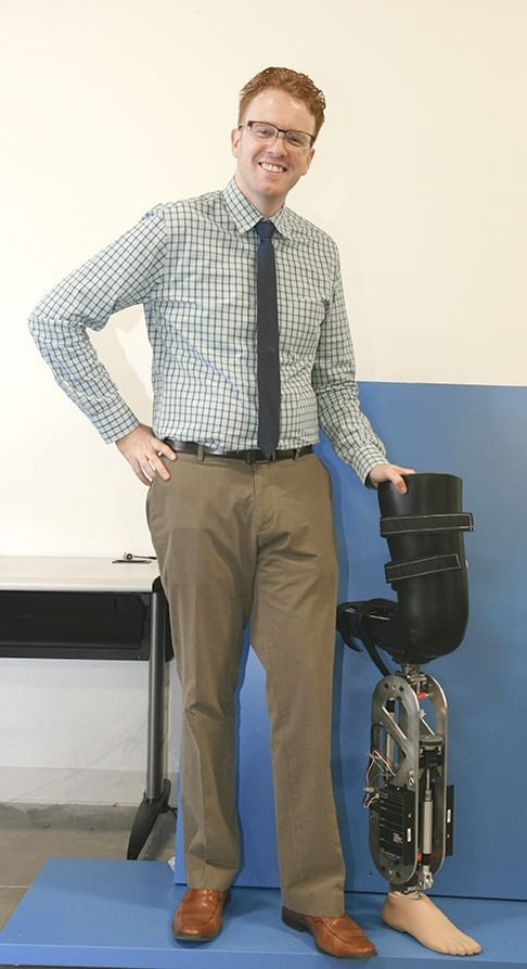 Dr. Robert Gregg stands next to a robotic leg that was designed by UTDesign students and is similar to the one reported in his research.