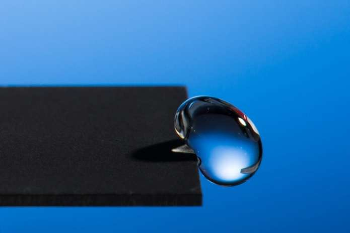 Professor Chunlei Guo has developed a technique that uses lasers to render materials hydrophobic, illustrated in this image of a water droplet bouncing off a treated sample. Photo by J. Adam Fenster / University of Rochester