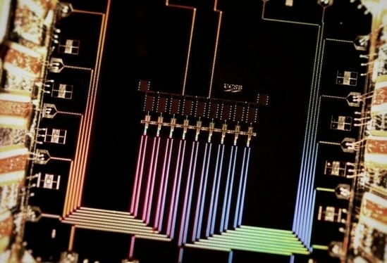 A photograph of the nine qubit device. The device conists of nine superconducting'Xmon' transmon in a row. Qubits interact with their nearest neighbors to detect and correct errors. Photo Credit: Julian Kelly