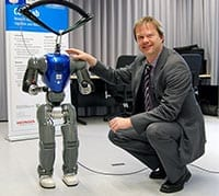 "The small humanoid robot COMAN still has some ""growing"" to do before it can interact ""eye to eye"" with human adults. Professor Dr. Jochen Steil is leading the new research project. Photo: Bielefeld University."
