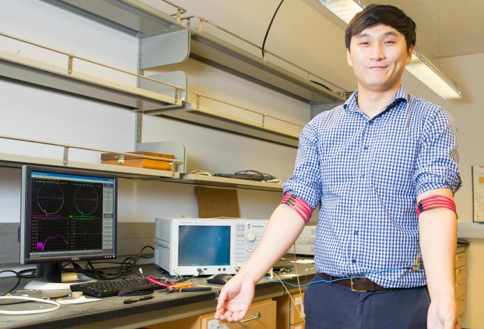 Jiwoong Park, an electrical engineering Ph.D. student and first author of the study, demonstrates communication from arm to arm using the magnetic field human body communication prototype developed in Mercier's Energy-Efficient Microsystems Lab at UC San Diego.