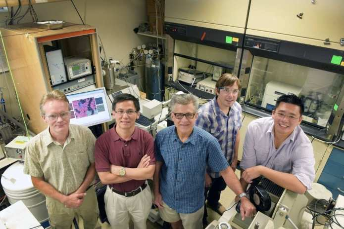 Sandia National Laboratories researchers, from right, Stan Chou, Bryan Kaehr, Jeff Brinker, Ping Lu and Eric Coker, gather in a lab where work on the catalyst molybdenum disulfide was achieved. (Photo by Randy Montoya)