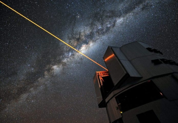"""A glowing laser shines forth from the European Southern Observatory's Very Large Telescope. Piercing the dark Chilean skies, its mission is to help astronomers explore the far reaches of the cosmos. ESO Photo Ambassador Gerhard Hüdepohl was on hand to capture the moment in a stunning portrait of modern science in action. We have all gazed up at the night sky and seen the stars gently twinkle as the Earth's turbulent atmosphere causes their light to shimmer. This is undoubtedly a beautiful sight, but it causes problems for astronomers, who want the crispest possible views. To help them achieve this, professional stargazers use something that sounds as though it has come from science fiction: a laser guide star that creates an artificial star 90 km above the surface of the Earth. The method by which it achieves this is nothing short of remarkable. The laser energises sodium atoms high in the Earth's mesosphere, causing them to glow and creating a bright dot that to observers on the ground appears to be a man-made star. Observations of how this """"star"""" twinkles are fed into the Very Large Telescope's adaptive optics system, controlling a deformable mirror in the telescope to restore the image of the star to a sharp point. By doing this, the system also compensates for the distorting effect of the atmosphere in the region around the artificial star. The end result is an exceptionally crisp view of the sky, allowing ESO astronomers to make stunning observations of the Universe, almost as though the VLT were above the atmosphere in space. Links Adaptive Optics and the Laser Guide Star: http://www.eso.org/public/teles-instr/technology/adaptive_optics.html ESO Photo Ambassadors"""