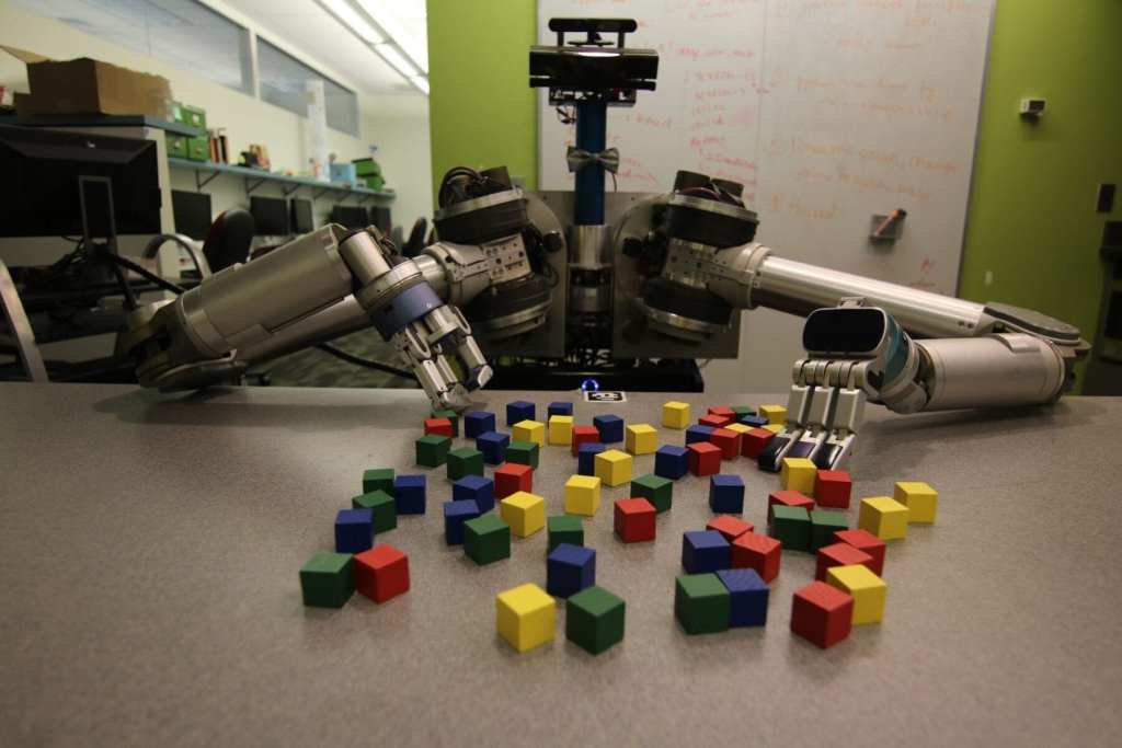 CMU researchers have developed an algorithm to help mobile robots decide which objects need to be picked up and moved and which ones can be safely pushed aside to accomplish a task. Here, the robot HERB uses it to pick up blocks