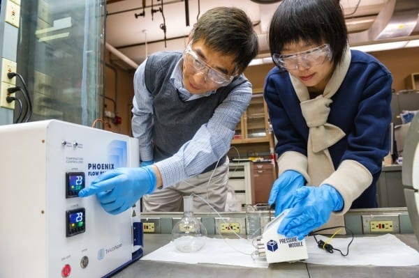 Argonne Principal Chemical Engineer Jie Li, left, and postdoctoral researcher Alina Yan create coated nanoparticles in a continuous flow reactor. Nanoparticles are key to an ongoing effort at Argonne to create more efficient window films.