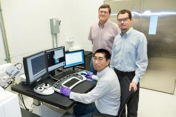 ORNL's Yang Song (seated), Dale Hensley (standing left) and Adam Rondinone examine a carbon nanospike sample with a scanning electron microscope.