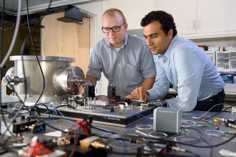 Post-doctoral scholar Peter McMahon, left, and visiting researcher Alireza Marandi examine a prototype of a new type of light-based computer. (Image credit: L.A. Cicero)