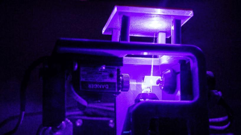 Laser beam transmitting upwards through glass.