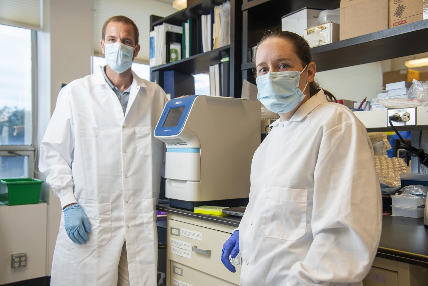 Jason Botten and Emily Bruce, who pioneered a streamlined COVID-19 test that doesn't use scarce chemicals, in their research lab in the University of Vermont's Larner College of Medicine. The machine between them is used to measure the presence and quantity of viral RNA in patient samples. (Photo: Brian Jenkins)