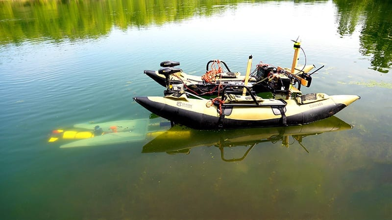 A yellow marine robot (left, underwater) finds its way to a mobile docking station to recharge and upload data before continuing a task. (Purdue University photo/Jared Pike)