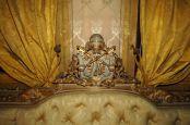 Cimasa intagliata a foglia oro su divani in capitonnèe, con imbottitura realizzata con crine animale.