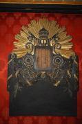 Cornice lignea porta stemma papale (mancante) con simboli e raggi solari in foglia oro.