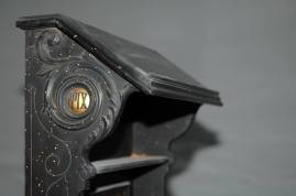 Inginocchiatoio formato da poggia-breviario in legno laccato nero e rollo poggia-ginocchi foderato con seta rossa.