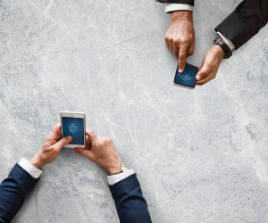 Hands of two men with cellphones on the table