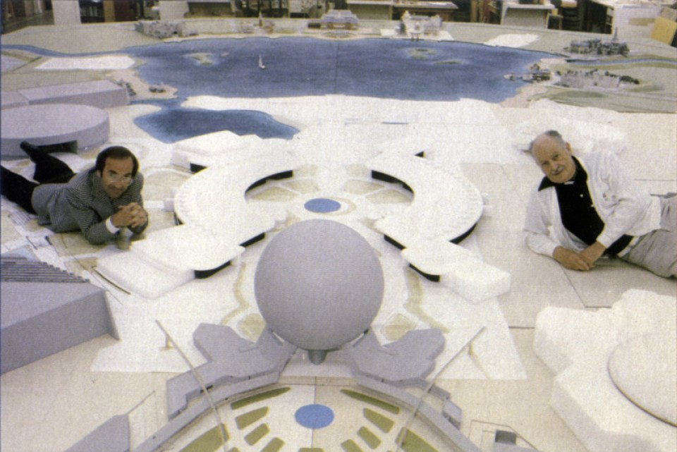 Marty (L) and John Hench (R) lounging on the scale model of Epcot Center