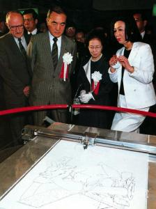 "In the US Pavilion at Tsukuba Expo 85, Japan Prime Minister Nakasone and company watch ""Aaron"" the robot draw. Photo courtesy James Ogul"