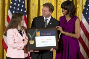 Discovery Cube CEO Joe Adams, center, accepting a 2013 2013 National Medal for Museum and Library Service from First Lady Michelle Obama
