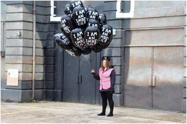 "A Dismal balloon seller, note the ears… Did you ever imagine that people would pay to carry a balloon proclaiming ""I am an imbecile""? Maybe Banksy doesn't like us after all."
