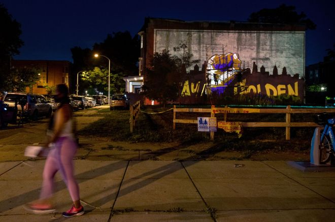 "Artists trace an image of their ""Stay Golden"" mural projected onto a blank wall in Strawberry Mansion. Artists Gerald Brown, Roberto Lugo, and Isaac Scott say they hope to ""activate the community, reflect on the radical energy in the city and around the country, and commemorate the powerful spirit of Black and brown people."" The words ""Stay Golden"" are reflective of a common usage of the color gold in African diasporic communities, and speak ""to the resilience of our people through adversity."""