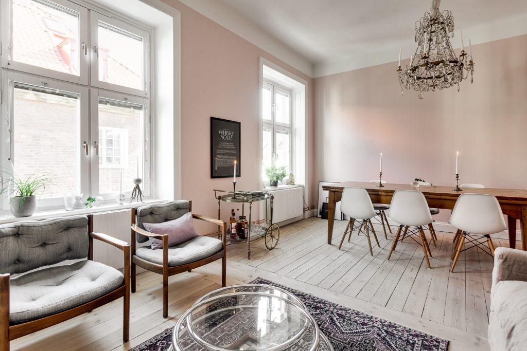 In deze mooie woonkamer zijn de muren roze geschilderd