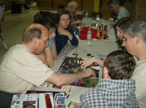 Luke (back to camera) playing in our first family game of Pandemic, with Mark K and John L., at GMT Weekend, April 2008