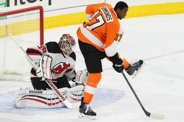 Right Winger Wayne Simmonds (#17) of the Philadelphia Flyers playing without a helmet screens Goalie Cory Schneider (#35) of the New Jersey Devils