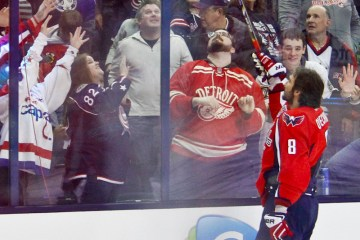 Alex Ovechkin of the Washington Capitals gives his stick to fans.