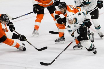 Defenseman Luke Schenn (#22) and Defenseman Michael Del Zotto (#15) of the Philadelphia Flyers battle for the puck against Right Wing Joonas Donskoi (#27) of the San Jose Sharks during the first period