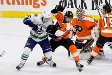 Center Bo Horvat (#53) of the Vancouver Canucks and Defenseman Shayne Gostibehere (#53) of the Philadelphia Flyers battles for the loose puck during the second period