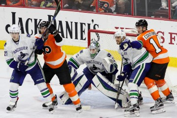 Players crowd the crease of Goalie Jacob Markstrom (#25) of the Vancouver Canucks during the third period