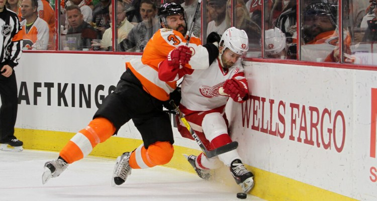Defenseman Radko Gudas (#3) of the Philadelphia Flyers checks Center Darren Helm (#43) of the Detroit Red Wings into the boards