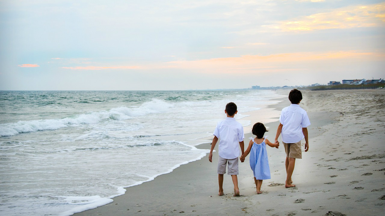 Three children walking shoeless along side an ocean on a beach at dusk. The left child is a boy in a white shirt and khaki shorts, the middle child is a girl in a blue dress, and the boy on the right is the tallest and also wears a white shirt with khakis. They all have black hair. Their backs face us, and the ocean is to the left. The sky is mostly clear with some clouds to the right that reflect the distant Sun. On the right off in the distance, there is tall green grass in front of a cluster of buildings.