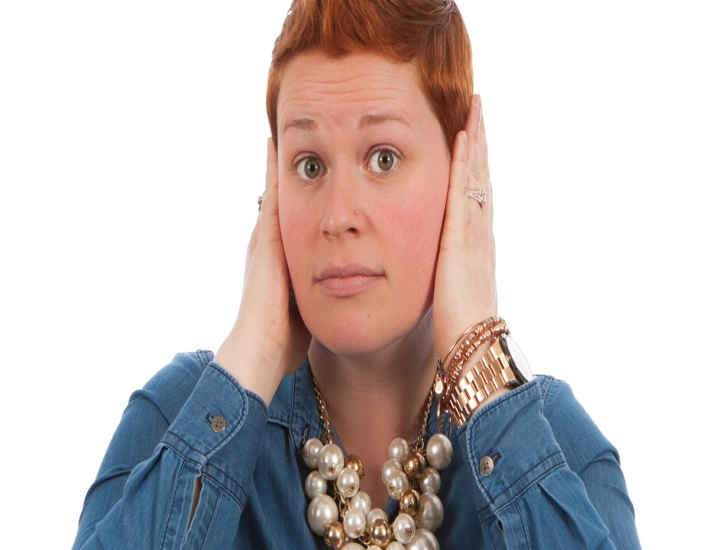 Woman covering her ears. She has short, reddish brown hair, raised eyebrows, wearing a denim shirt, big necklace and a bracelet.