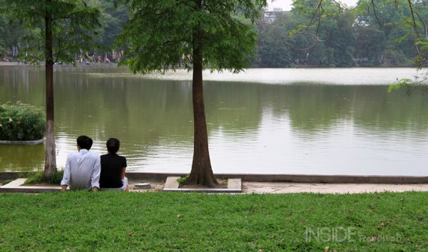 A couple sit on the edge of the lake