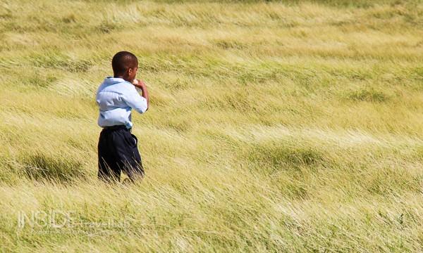 Child runs through grass in Antigua