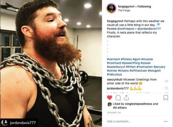 Man wears chains around his chest while working out in an Instagram Post from The Forge Gym.