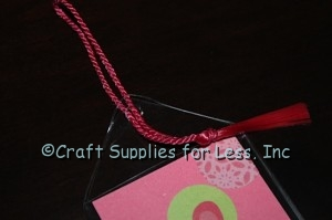add floss bookmark tassel to the top of vinyl bookmark sleeve