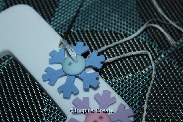 It's easy to sew buttons onto craft foam!  Great for embellishing snowflake frames.
