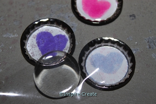 Add clear epoxy stickers to the center of bottle caps