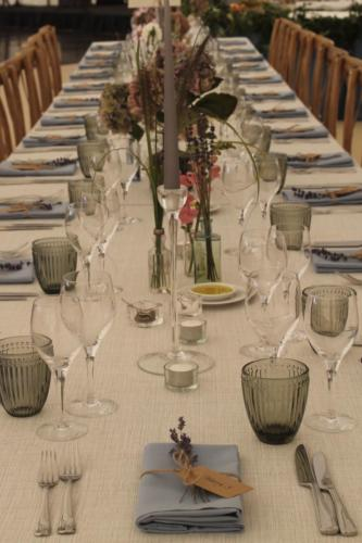 Long dining tables and random mini vases and vessels of botanical specimens