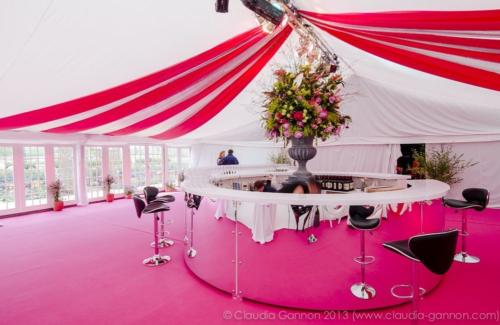 Fuchsia carpet and swagged ceiling in a framed marquee.  Silver round mirrored bar.