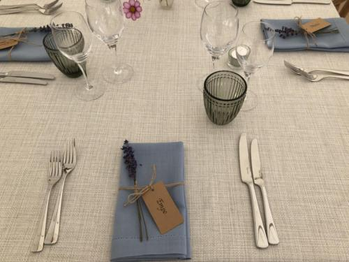 Hemstitched cornflower blue napkin, dusky grey water glasses, beautiful textured table linen.