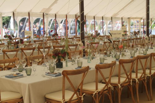 Traditional pole tent set for wedding with long dining tables and cross back chairs
