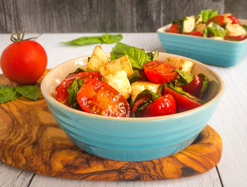 Caprese Salad in a blue bowl on top of a wood cutting board with a tomato and basil in the background.