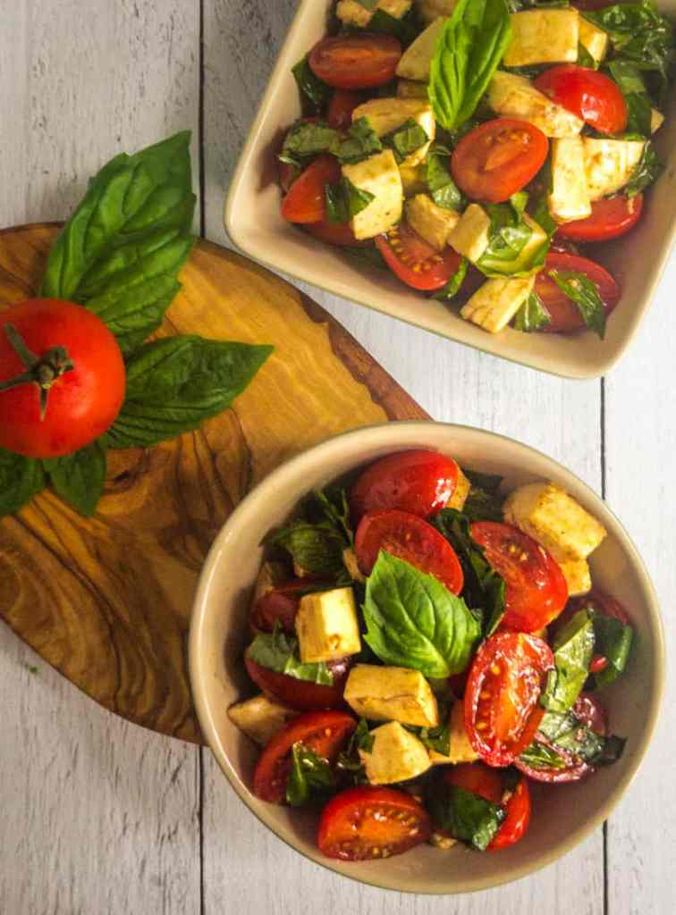 Overhead shot of Caprese Salad in bowls with a tomato and basil on a small cutting board.