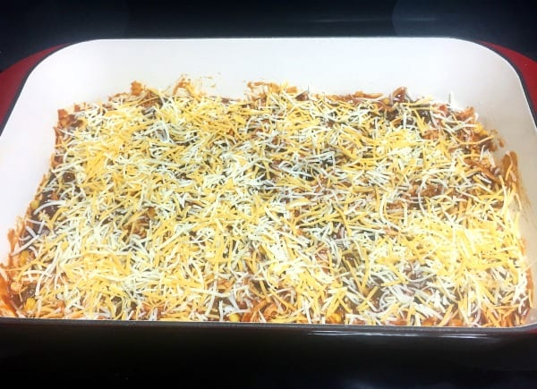 Adding the shredded cheese to the layers of chicken enchilada casserole