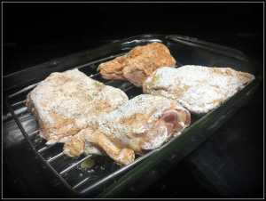 crispy oven-baked chicken thighs on a rack in a roasting pan in the oven
