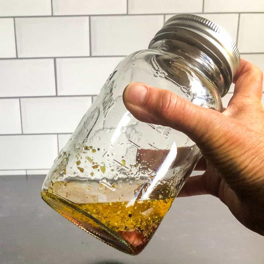 Hand shaking the vinaigrette in a mason jar.